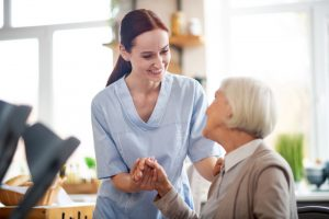 Red-haired caregiver smiling and talking to aged woman