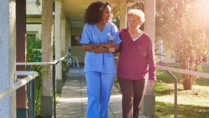 African female doctor talking to elderly retired woman in the hospital yard. Happiness and retirement concept.