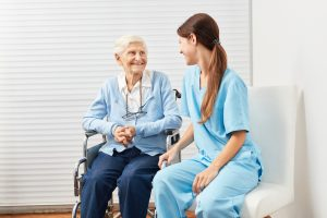 Old senior woman in a wheelchair with a nurse at home nursing