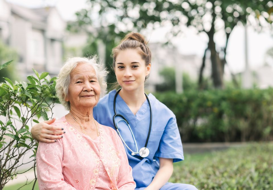 Nurse caregiver embracing happy Asian elderly woman outdoor in the park. Focused on eldery woman