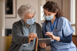 Old woman with nurse with surgical mask and using digital tablet during coronavirus pandemic