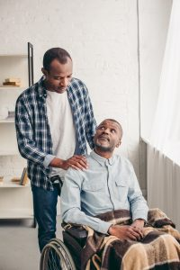 adult african american son looking at disabled senior father in wheelchair - Care Partners