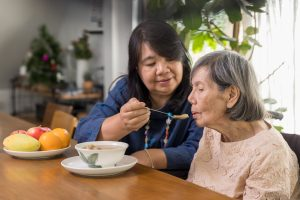 Daughter feeding elderly mother with soup - Care Partners