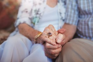 Cropped shot of elderly couple holding hands while sitting together at home - Care Partners